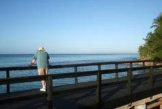 Overlooking the Ocean. A man standing on a pier overlooking the ocean Royalty Free Stock Photos