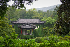 Overlooking tranquility. Traditional Chinese building with balcony in idyllic garden overlooking lush greenery. A serene, peaceful setting that is calm and Stock Photo