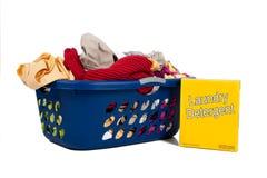Overlopende wasmand met detergens stock afbeeldingen