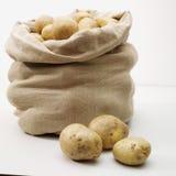 Overlopende zak van potatos op whit stock afbeelding
