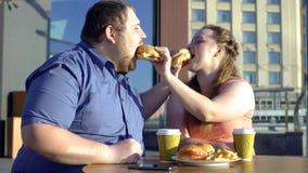 Overmaats paar die burgers delen tijdens romantische datum in openlucht, calorieën en dieet royalty-vrije stock afbeeldingen