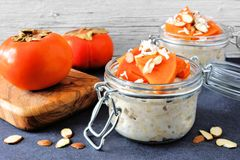 Overnight breakfast oatmeal with persimmons, table scene. Overnight breakfast oatmeal with persimmons, almonds and coconut. Side view table scene on a dark Royalty Free Stock Image