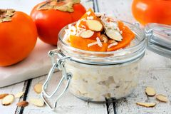 Overnight breakfast oatmeal with persimmons, table scene on rustic wood. Overnight breakfast oatmeal with persimmons, almonds and coconut. Side view table scene Royalty Free Stock Photo