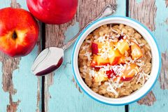 Overnight breakfast oats with peach and coconut on rustic wood Royalty Free Stock Images