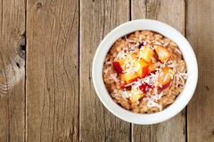 Overnight breakfast oats with peach and coconut on rustic wood Stock Image