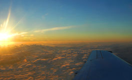 Overnight Flight to Hawaii. Morning sunlight burns across the clouds painting them orange and golden.  Airplane wing cuts across bottom of image.  Overnight Stock Images