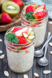 Overnight oatmeal with fresh strawberry and kiwi in glass jar Stock Image