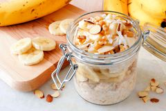 Overnight oats with bananas and nuts on white marble. Overnight oats with bananas and nuts in snap lid glass jar on white marble Royalty Free Stock Images