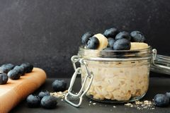 Overnight oats with blueberries and bananas against a dark background. Overnight oats with fresh blueberries and bananas in a jar against a dark background Royalty Free Stock Image