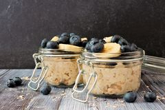 Overnight oats with blueberries and bananas on a dark background. Overnight oats with fresh blueberries and bananas in jars on a rustic dark background Royalty Free Stock Photos