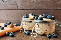 Overnight oats with blueberries and bananas on rustic wood. Overnight oats with fresh blueberries and bananas in a snap lid jar on a rustic wood background Stock Photo