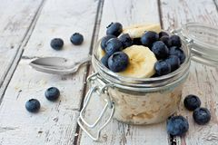 Overnight oats with blueberries and bananas on a white wood background. Overnight oats with fresh blueberries and bananas in a jar on a rustic white wood Royalty Free Stock Image