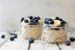 Overnight oats with blueberries and bananas on a white wood background. Overnight oats with fresh blueberries and bananas in jars on a rustic white wood Royalty Free Stock Image