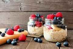 Overnight oats with blueberries and raspberries in jars on rustic wood. Overnight oats with fresh blueberries and raspberries in jars on a rustic wood background royalty free stock photos