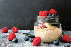 Overnight oats with blueberries and raspberries, scene on dark background Stock Photo