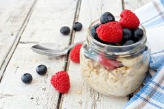 Overnight oats with blueberries and raspberries on a white wood background. Overnight oats with fresh blueberries and raspberries in a jar on a rustic white wood Royalty Free Stock Images