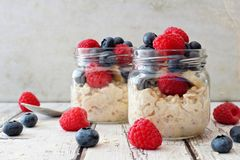 Overnight oats with blueberries and raspberries on a white wood background. Overnight oats with fresh blueberries and raspberries in jars on a rustic white wood Stock Photos