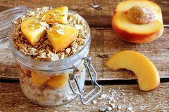 Overnight oats with peaches and granola on rustic wood Stock Photos