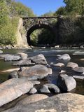 Overpass bridge with river running through it. Stone overpass bridge with river running through it and silky smooth water Stock Photo