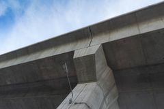 Overpass concrete with light below view on blue sky background. Under view of overpass highway with blue sky in background Stock Images