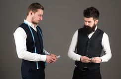 Overpayment concept. Tailor, greedy designer wants more money. For expensive clothes. Customer, client paying, counting money, grey background. Man with beard Royalty Free Stock Photo