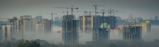 Depressing cityscape with construction of new buildings. Overpopulation concept - construction of new block bulidings, fog, toned, Kyiv, Ukraine Stock Photos