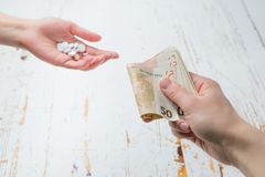 Overpriced drugs concept - hands exchanging money for drugs. Medicine or insurance related crime concept. Copy space royalty free stock image