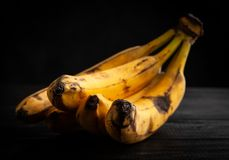 Overripe spotted bananas. On dark background royalty free stock images