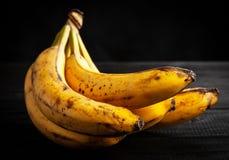 Overripe spotted bananas. On dark background stock photo