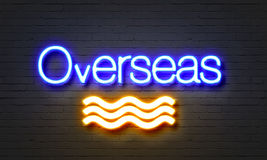 Overseas neon sign on brick wall background. Stock Photography