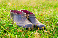 Overshoes on a glade. Rubber overshoes stand on a glade Stock Photo