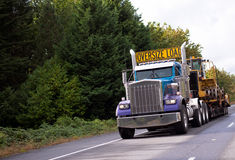 Oversize load big rig classic semi truck with step down flat bed. The big powerful rig semi truck with a sign Oversize load on the cab roof and special flat bed Stock Photos