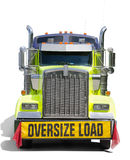 Wide OVERSIZE LOAD sign semi tractor truck isolated. A big semi tractor 18 wheel truck with a big wide OVERSIZE LOAD banner and red flags on the front of the Royalty Free Stock Photo