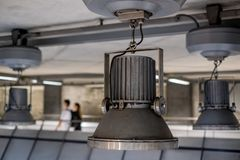 Oversized industrial style pendant lights hanging in Westminster Underground Station, London, UK stock photo
