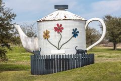 Oversized tea kettle with two black cats in front yard of Texas. Teachers, cat. Oversized tea kettle with two black cats in front yard of Texas home royalty free stock photo