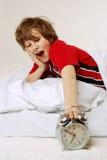 Oversleep. Awaking boy turns off the alarm clock, screaming Royalty Free Stock Photo