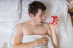 Oversleep concept. Young man is waking up and looking on alarm clock. Stock Images