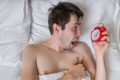 Oversleep concept. Young stressed man is waking up and is shoked. Stock Photography