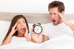 Oversleeping - horrified couple have overslept. Oversleeping. Attractive young couple missed the ringing of the alarm clock and have overslept awakening and are Stock Photography