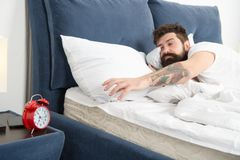 Overslept снова Подсказки для просыпать вверх предыдущее Кровать стороны бородатого хипстера человека сонная с будильником Поверн стоковые фото