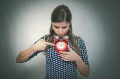 Overslept chocó a la mujer con el despertador rojo en fondo gris oversleep rezagado fotografía de archivo libre de regalías