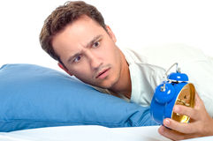 Overslept man looking at blue alarm clock horrified Royalty Free Stock Images