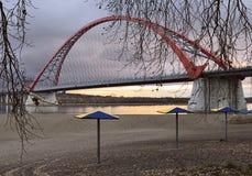 Overspannen brug over de Ob-Rivier met strandparaplu's stock fotografie