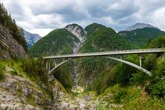 Overspannen brug over een kloof van de bergrivier in Europese Alpen met berg in achtergrond en bewolkte hemel stock afbeeldingen