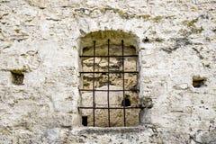 Overspannen venster met metaalbars in oud metselwerk De oude helft-geru?neerde synagoge royalty-vrije stock afbeelding