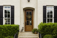 Overspannen voordeur met standbeeld en struiken stock afbeeldingen