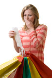Overspending. Attractive blond woman standing in front of a bunch of colorful shopping bags checking over the receit with a worried expression Royalty Free Stock Images
