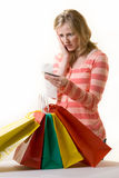 Overspending. Attractive blond woman standing in front of a bunch of colorful shopping bags checking over the receit with a worried expression royalty free stock photos