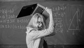 Overstrain of the nervous system. Teacher woman raising laptop above herself ready to destroy. She needs pills to keep. Calm and mental health. Working royalty free stock images