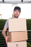 Overstrained postman with parcels Royalty Free Stock Images